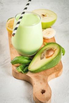 健康食品。食事の朝食または軽食。ヨーグルト、アボカド、バナナ、リンゴ、ほうれん草、レモンのグリーンスムージー。食材を使った白いコンクリートの石のテーブルの上。コピースペース