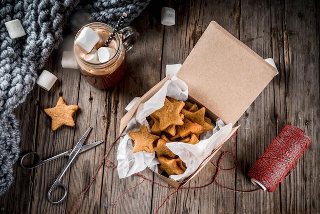 伝統的な秋冬の飲み物とおやつ。マシュマロとジンジャービスケットの星、ギフトボックス、古い素朴な木製のテーブルとホットチョコレートのカップ。居心地の良い雰囲気、トップビュー、