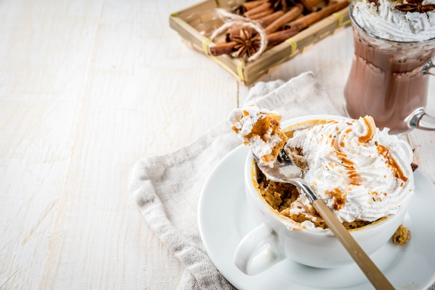 Рецепты с тыквой, фаст-фуд, микроволновая еда. острый тыквенный пирог в кружке, со взбитыми сливками, мороженым, корицей, анисом. на белом деревянном столе, с чашкой горячего шоколада.