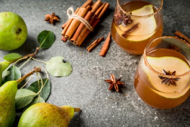 秋の飲み物。グリューワイン。ナシ、サイダー、チョコレートシロップ、シナモン、アニス、ブラウンシュガーと伝統的な秋のスパイシーなカクテル。黒い石のテーブルの上。
