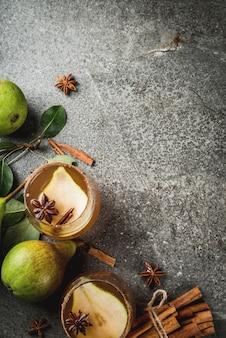 秋の飲み物。グリューワイン。ナシ、サイダー、チョコレートシロップ、シナモン、アニス、ブラウンシュガーと伝統的な秋のスパイシーなカクテル。黒い石のテーブルの上。上面図