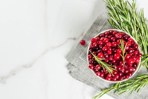 秋と冬のカクテル、ローズマリーの枝、白い大理石のテーブル、トップビューでクランベリーの成分
