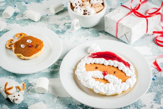 子供のクリスマスの朝食のアイデア:サンタクロースと鹿のようなパンケーキ、テディベアと鹿のマシュマロとココア。クリスマスギフト付きの明るい青のコンクリート表面