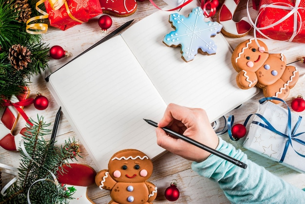 Праздничная рождественская деревянная белая поверхность, с ветвями елки, сосновыми шишками, украшениями, рождественскими подарками, пряниками и блокнотом, рука девушки пишет на картинке над копией пространства