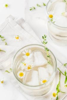 夏のさわやかなドリンク、注入されたハーブ水、アイスティー。白い大理石のテーブルの上に、カモミールハニーとグラスにタイムを添えたウイスキーカクテル。コピースペーストップビュー