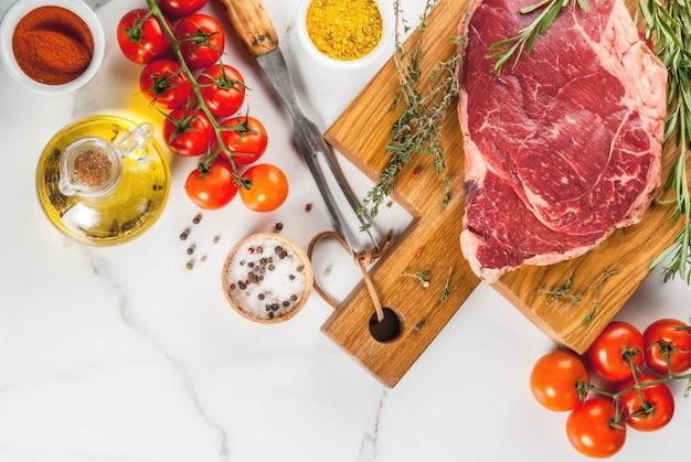 新鮮な生の肉、まな板の上の羊肉ビーフステーキ、調理用の食材。白い大理石のテーブルにコピースペース平面図