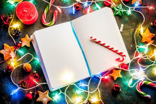 Поверхность рождества темная с гирляндой рождества, украшениями, звездами пряника и свечами. копия сверху, с блокнотом для желающих