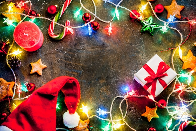 Темный фон рождество с рождественские гирлянды, украшения, пряники звезд, подарочная коробка и шляпу санта и свечи. вид сверху копировать пространство кадра