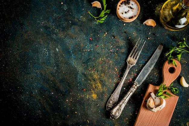 Концепция приготовления пищи, специи, травы и масла для приготовления обеда, с разделочной доской, столовым ножом и вилкой, копией пространства вид сверху