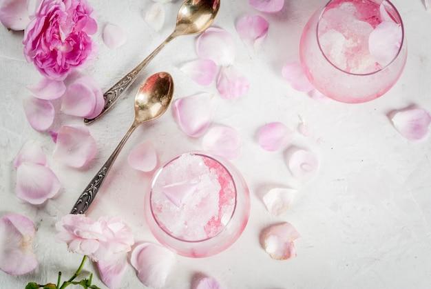 Летние освежающие десерты. вегетарианское диетическое питание. мороженое замороженное розовое, замороженное, с лепестками роз и розовое вино. белый бетонный стол, с ложками, полосатой соломкой, лепестками и цветами. скопировать вид сверху