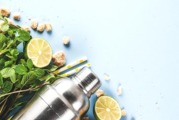 カクテルモヒートまたはレモネードの材料-レモン、ライム、ミント、砂糖、シェーカーとカクテルストロー。水色の表面コピースペーストップビュー