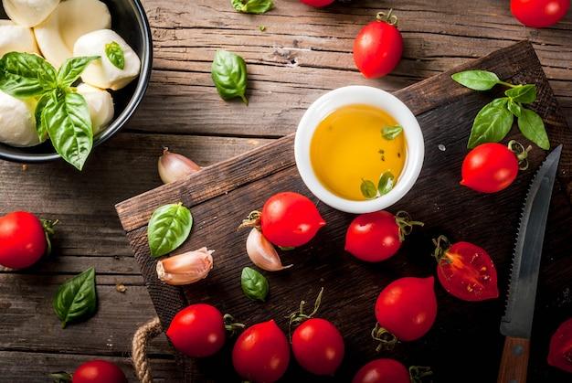 農場の生のオーガニック製品。イタリアンスタイルのディナーの準備。カプレーゼサラダ、パスタ、ピザの材料。バジル、トマト、モッツァレラチーズ、古い木製のテーブルにオリーブオイル。