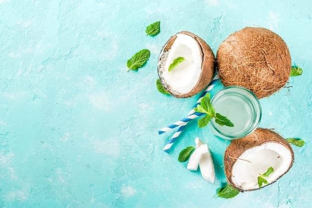 健康食品のコンセプト。ココナッツ、アイスキューブ、ミント、新鮮な有機ココナッツ水、明るい青の表面、コピースペース平面図