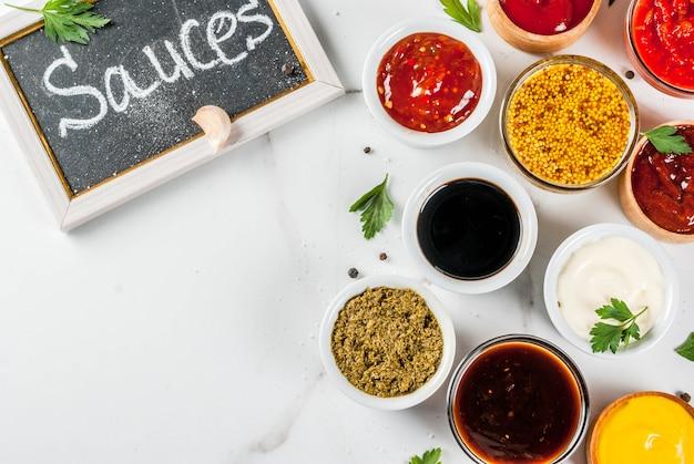 Набор различных соусов - кетчуп, майонез, шашлык, соя, терияки, горчица, хлебные горки, песто, аджика, чатни, ткемали, гранатовый соус на белой мраморной поверхности. вид сверху копией пространства