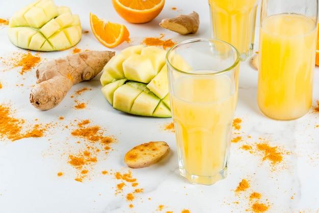 インド料理のレシピ。健康食品、デトックス水。白い大理石のテーブルの上の伝統的なインドのマンゴー、オレンジ、ターメリック、ジンジャーのスムージー。コピースペース