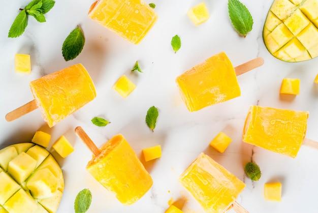 アイスクリーム、アイスキャンディー。オーガニック食材、デザート。白い大理石のテーブルにミントの葉と新鮮なマンゴーフルーツを添えた冷凍マンゴースムージー。コピースペーストップビュー