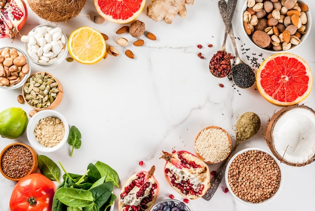 有機健康ダイエット食品、スーパーフード-豆、マメ科植物、ナッツ、種子、野菜、果物、野菜のセット。白い表面コピースペース。トップビューフレーム