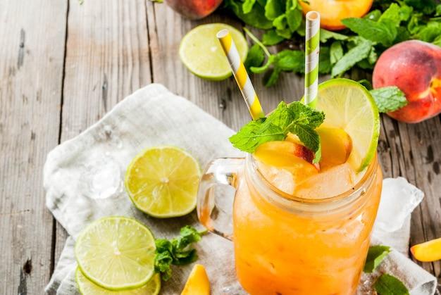 Летние напитки, коктейли. веганская еда. персиковые смузи, сок или лимонад. в банке с масоном, с лаймом, рубленым льдом и листьями мяты. на старый деревенский деревянный столик с ингредиентами. копировать пространство