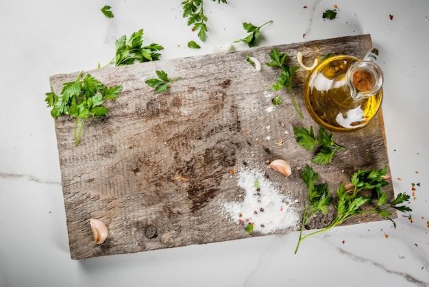 Еда приготовления фона. старая разделочная доска на белом мраморном кухонном столе. оливковое масло, нож, специи, соль, перец, чеснок, петрушка. вид сверху копией пространства