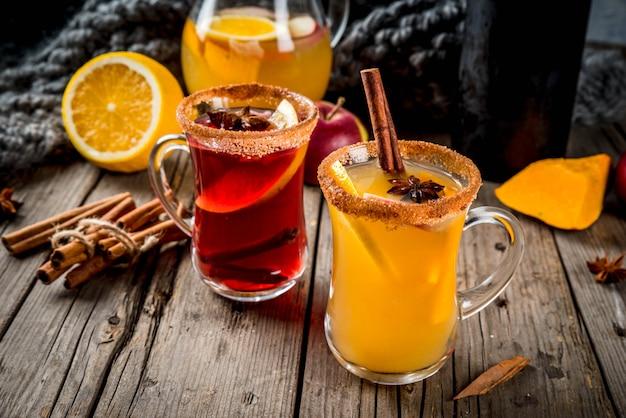 伝統的な秋と冬の飲み物とカクテル。アニス、シナモン、リンゴ、オレンジ、ワインと白と赤の秋の辛いサングリア。ガラスのマグカップ、古い素朴な木製のテーブル。セレクティブフォーカスコピースペース