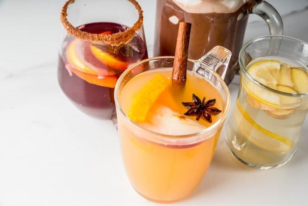 さまざまな秋の伝統的な飲み物のセレクション:マシュマロ入りホットチョコレート、レモンとジンジャー入りの紅茶、白パンプキンのスパイシーなサングリア、ホットワイン。白い大理石のテーブル、コピースペース、セレクティブフォーカス