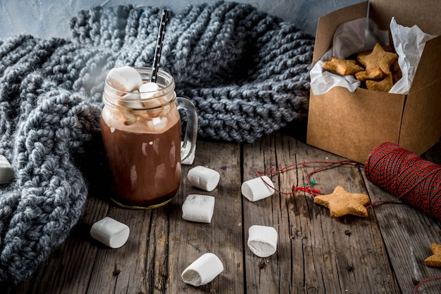 伝統的な秋冬の飲み物とおやつ。マシュマロとジンジャービスケットの星、ギフトボックス、古い素朴な木製のテーブルとホットチョコレートのカップ。居心地の良い雰囲気、コピースペース