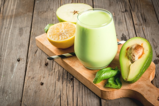健康食品。食事の朝食または軽食。ヨーグルト、アボカド、バナナ、リンゴ、ほうれん草、レモンのグリーンスムージー。食材を使った素朴な木製のテーブルの上。コピースペース