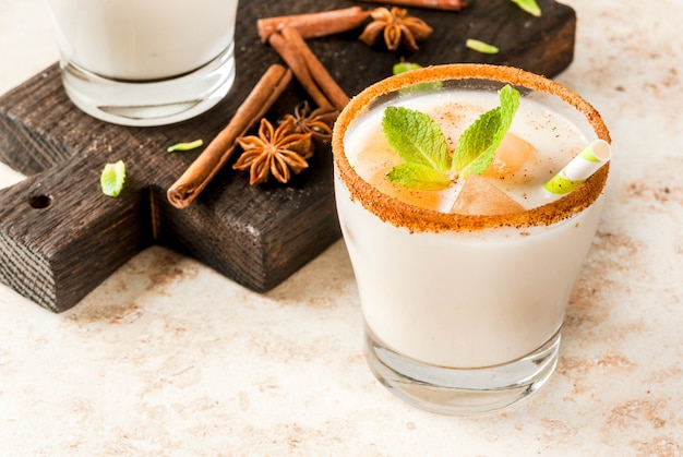 インドの伝統的な飲み物は、チャイ、ミルク、ミントの葉のアイスキューブを添えたアイスティーまたはチャイマサラです。木の板に縞模様のストローで。ライトベージュの石のテーブルの上。コピースペース