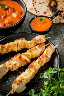 インド料理。伝統的な料理のスパイシーなチキンティッカマサラ、バターチキンカレー、インドのナンバターパン、スパイス、ハーブ。ボウルで提供しています。ソース、串焼き。石の暗いテーブル。コピースペース