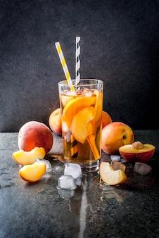 夏の飲み物。ネクタリンのオーガニックの自家製ピーチ入りアイスティー。氷と食材を使った黒い石の背景。コピースペース