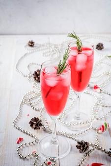 お正月、クリスマスの飲み物。クランベリー、リキュール、ローズマリー、氷と赤いアルコールカクテル。クリスマスキャンディー、装飾品、松ぼっくりのある白いテーブル。コピースペース