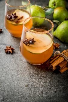 秋の飲み物。グリューワイン。ナシ、サイダー、チョコレートシロップ、シナモン、アニス、ブラウンシュガーと伝統的な秋のスパイシーなカクテル。黒い石のテーブルの上。コピースペース