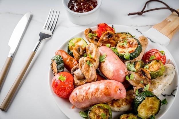バーベキュー。野菜バーベキューきのこ、トマト、ズッキーニ、タマネギとさまざまな肉のグリルソーセージの品揃え。白い大理石のテーブルの上、皿の上、ソース付き。コピースペース