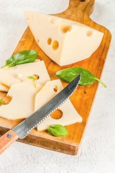 バジルの葉とまな板の上のマースダムチーズ