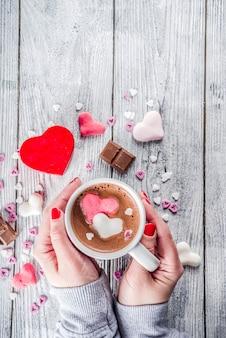 Руки девушки держат горячий шоколад с сердечками из зефира