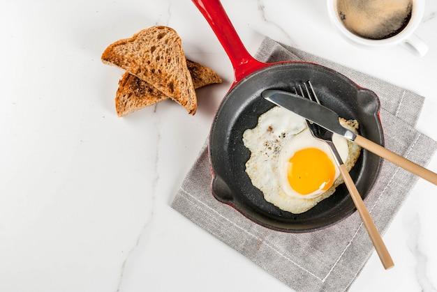 トーストしたパン、鉄鍋で揚げた卵、コーヒーの朝食