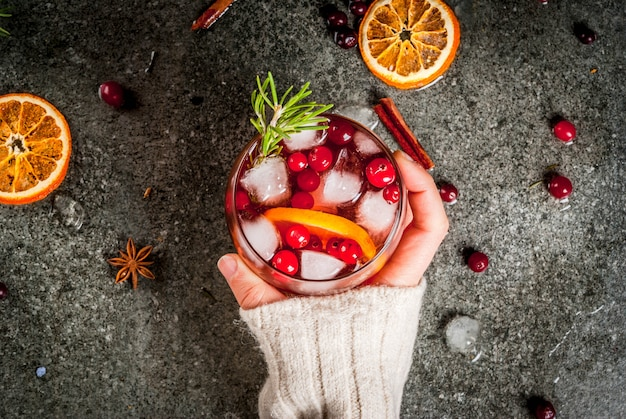 女性はクランベリー、オレンジ、ローズマリー、スパイスと冷たいカクテルを飲む