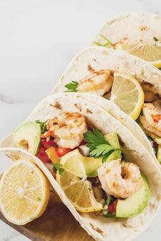 伝統的な自家製サラダ、パセリ、新鮮なレモン、アボカド、エビのグリルのトルティーヤタコス