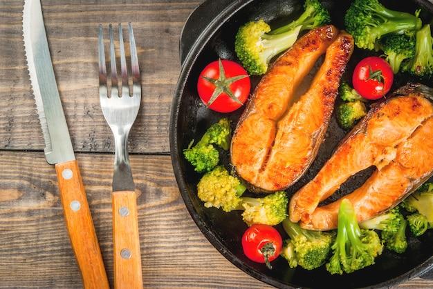Здоровое питание, диета. запеченная форель на гриле (лосось) с овощным гарниром - брокколи, помидорами. в порционной сковороде, на деревянном столе. вид сверху копией пространства
