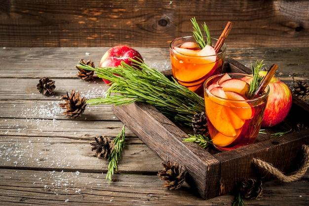 クリスマス、感謝祭の飲み物。秋、冬のカクテルグロッグ、ホットサングリア、ホットワイン-アップル、ローズマリー、シナモン、アニス。古い素朴な木製のテーブル、トレイ。コーン、ローズマリーの枝。コピースペース