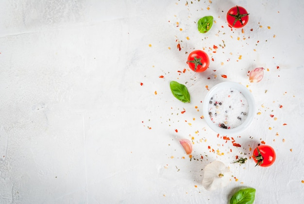 食品の背景。ランチを調理するための材料、野菜、スパイス。新鮮なバジルの葉、トマト、ニンニク、玉ねぎ、塩、コショウ。白い石のテーブルの上。コピースペースのトップビュー
