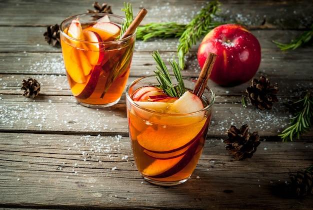 クリスマス、感謝祭の飲み物。秋、冬のカクテルグロッグ、ホットサングリア、ホットワイン-アップル、ローズマリー、シナモン、アニス。古い素朴な木製のテーブル。コーン、ローズマリーの枝。コピースペース