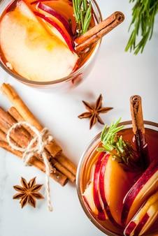 クリスマス、感謝祭の飲み物。秋、冬のカクテルグロッグ、ホットサングリア、ホットワイン-アップル、ローズマリー、シナモン、アニス。白い大理石のテーブルの上。コーン、ローズマリー。コピースペースのトップビュー
