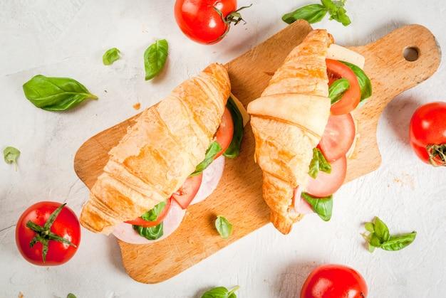 軽くてボリュームのある春の朝食。ハム、チーズ、フレッシュトマト、バジルのクロワッサン。白い石のテーブルの上に、材料が入っています。コピースペースのトップビュー