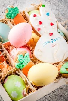イースター休暇の概念、ニンジンの形で甘いクッキー、イースターのウサギ、カラフルな卵、表示を閉じる