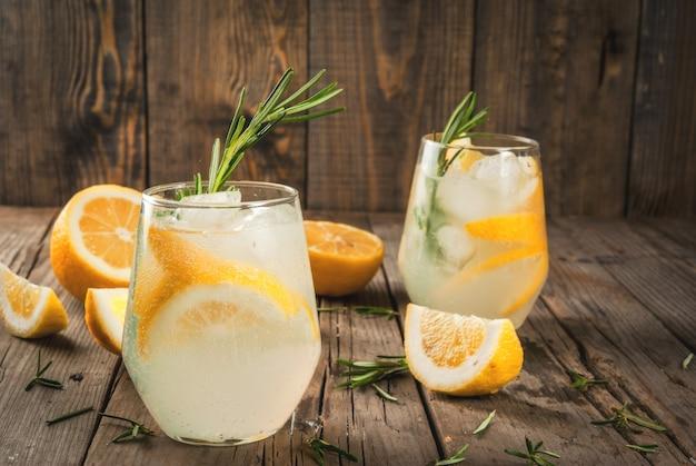 夏の軽食。デトックスウォーター。レモネード。古い木製の素朴なテーブルの上の氷、レモン、ローズマリーのトニック。コピースペース