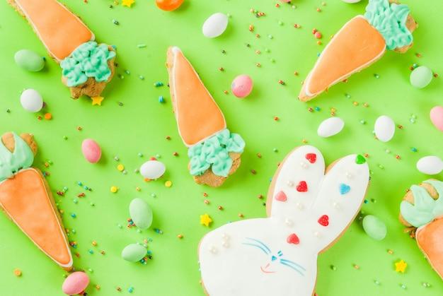 イースターホリデーのコンセプト、ニンジン、イースターのウサギ、甘い振りかけると卵キャンディーの形で甘いクッキー、明るい緑の背景コピースペース平面図、グリーティングカードの背景