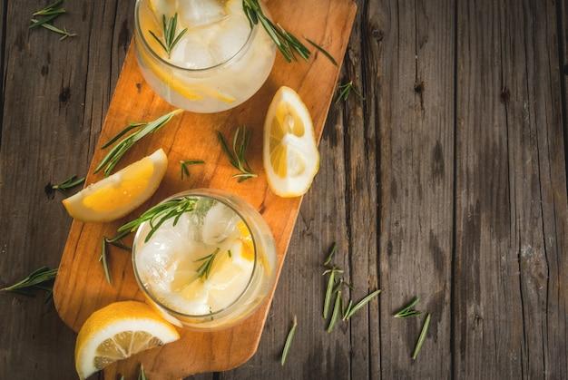 夏の軽食。デトックスウォーター。レモネード。古い木製の素朴なテーブルの上の氷、レモン、ローズマリーのトニック。コピースペースのトップビュー