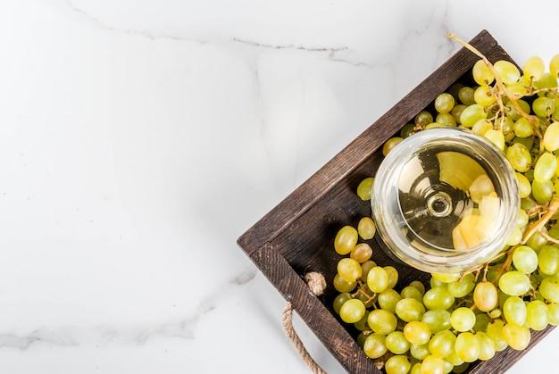 Белый виноград и белое вино в бокале, в деревянном подносе на белом мраморном столе. скопировать вид сверху