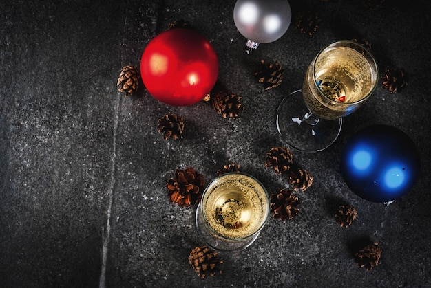 Сухое шампанское в бокалах, рождественские разноцветные шарики, сосновые шишки, новогодний натюрморт композиция на темном фоне каменных, выборочный фокус копией пространства вид сверху
